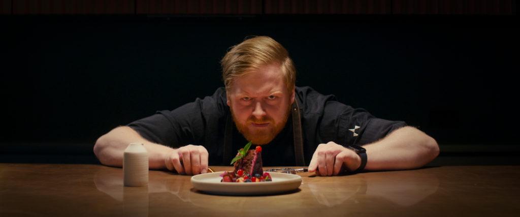 Koch schaut akribisch auf einen Dessertteller, der vor ihm steht.