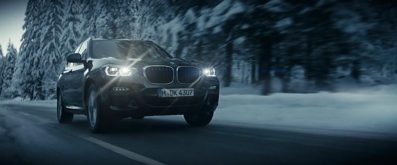 Bild eines BMW X5 SUV bei der Fahrt durch einen verschneiten Wald