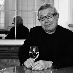Foto von Daniel Liebeskind mit einem Glas in der Hand und einem Spiegel im Hintergrund