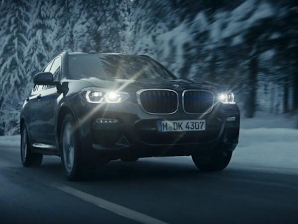 Auto auf einer Straße mit einem verschneiten Wald im Hintergrund
