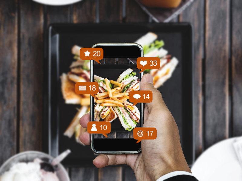 Handy macht ein Foto von dem Essen, welches auf einem Tablet dadrunter liegt