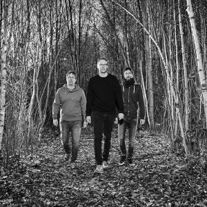 matthias-vogt-trio-laeuft-durch-wald-in-schwarz-weiss