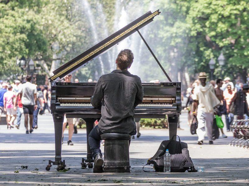 Mann am Klavier von hinten fotografiert mit vielen Menschen im Hintergrund