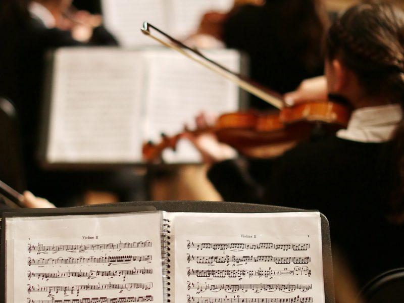 Notenständer mit Noten und einem Orchester im Hintergrund